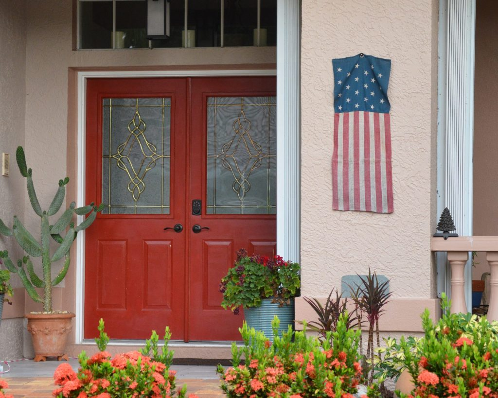red front door with a stylized American flag hanging beside it