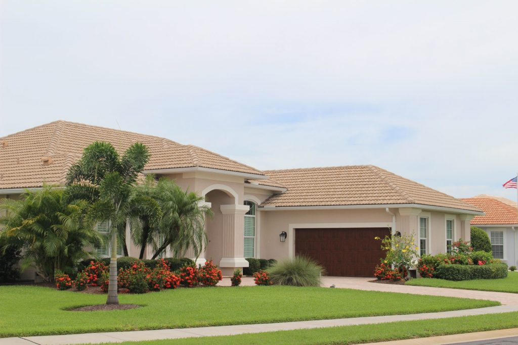 a large, tan home with a palm tree