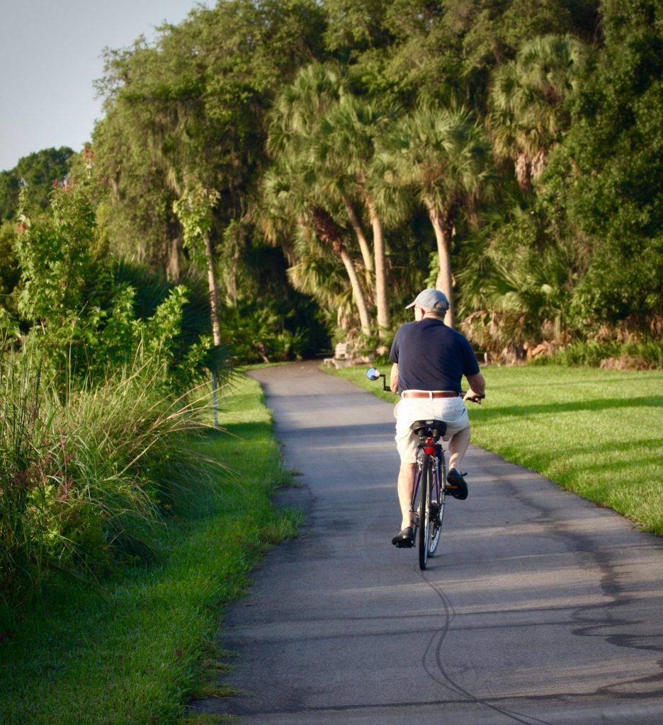 man riding his bike along a paved path