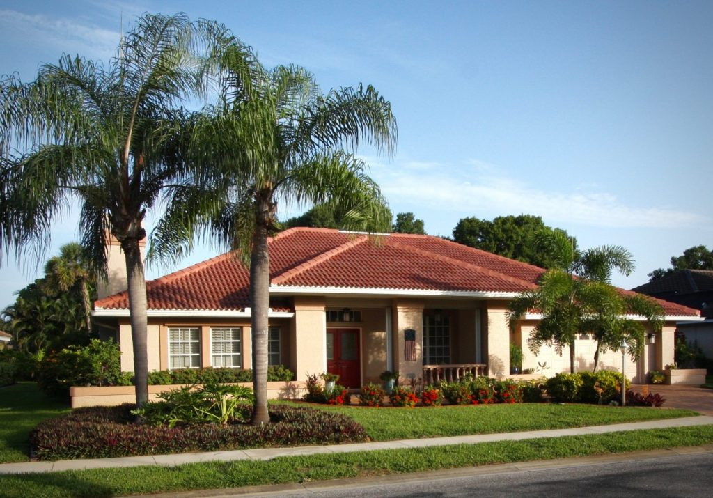 home with a terra cotta colored tile roof behind two palm trees