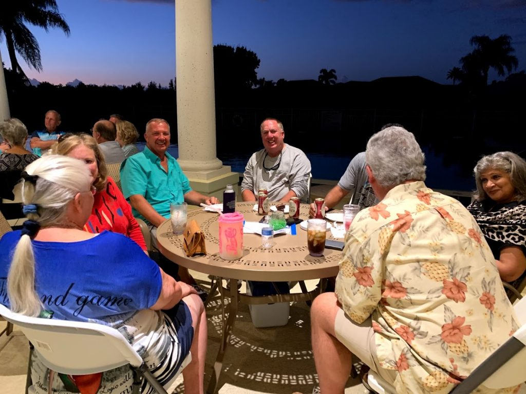 group of people sitting next to the pool at the LOJ clubhouse