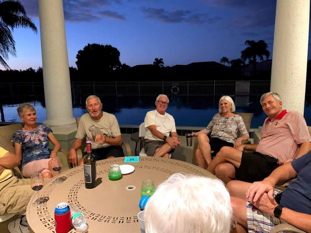 group of people at a table near the pool at the clubhouse