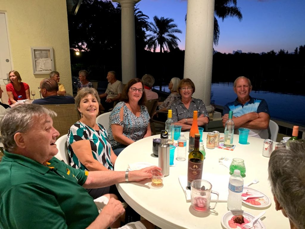 group of people enjoying beverages near the pool at the clubhouse