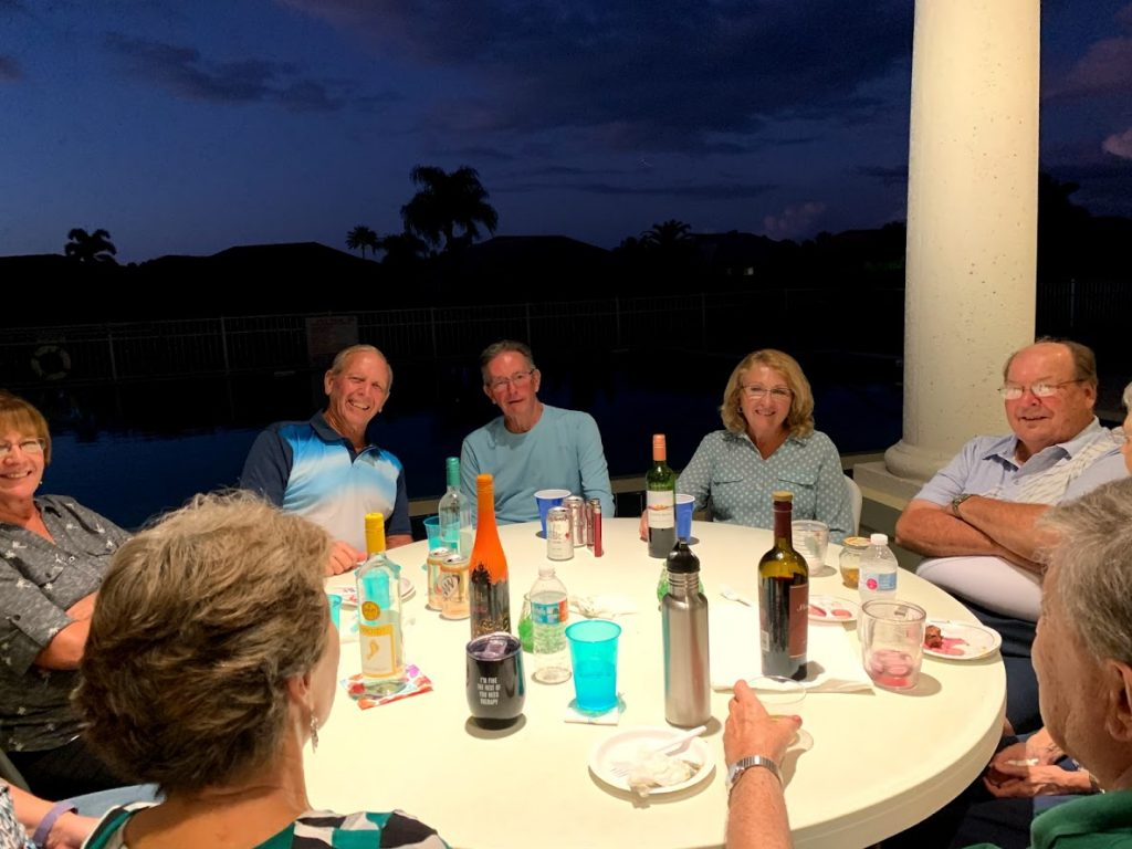 group of people enjoying beverages at the clubhouse at dusk